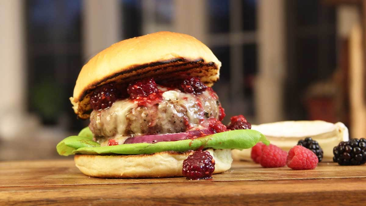 brie and berry burger on a cutting board