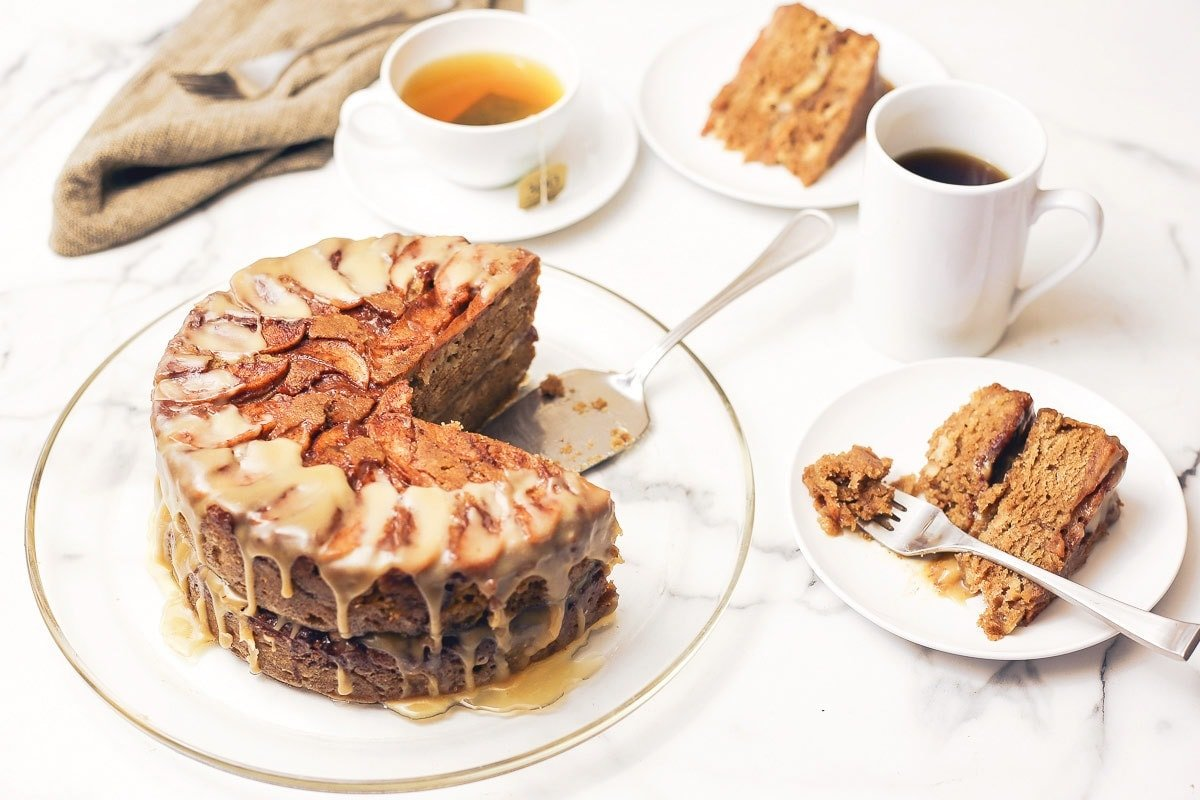 Apple Cake on a plate with coffee and tea and 2 slices on white plates
