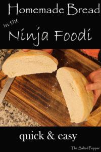 Homemade bread in the Ninja Foodi cut in half on a cutting board
