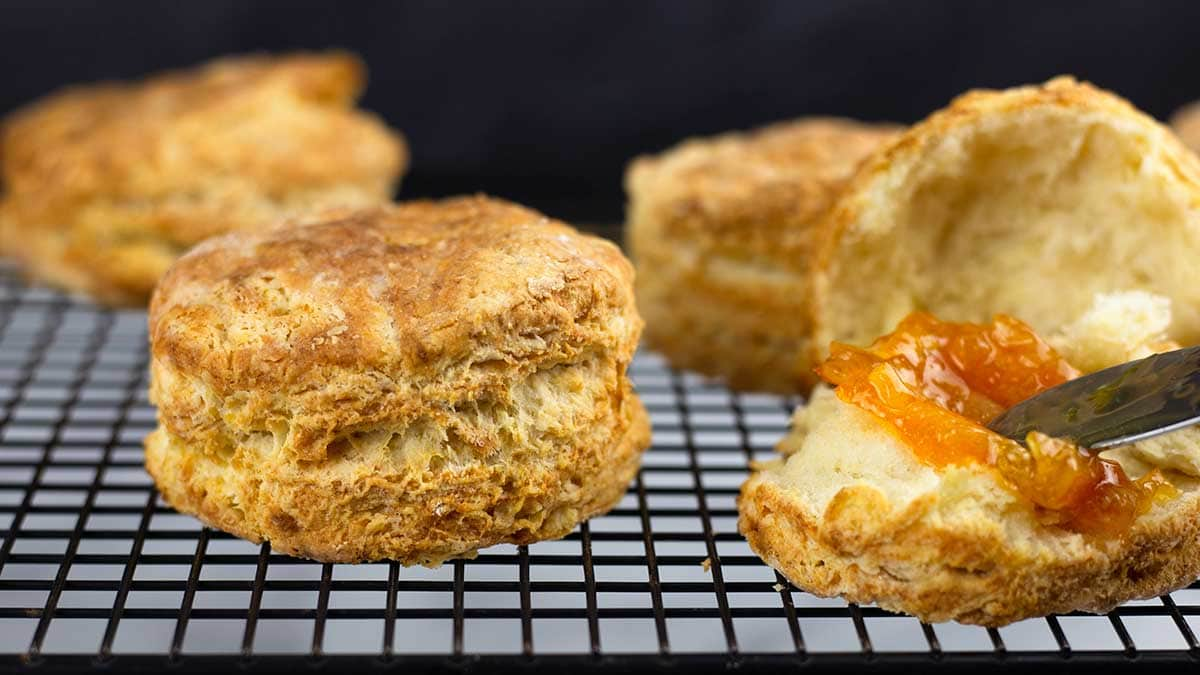 Homemade biscuits on a cooling rack with orange marmalade on one