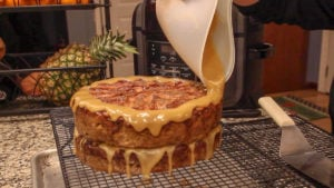 Ninja Foodi Recipe Apple Cake Pouring Icing over top of cake