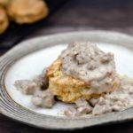 Sausage gravy on top of a biscuit on a plate