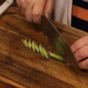 Cajun Jambalaya in the Ninja Foodi slicing green onions on the bias
