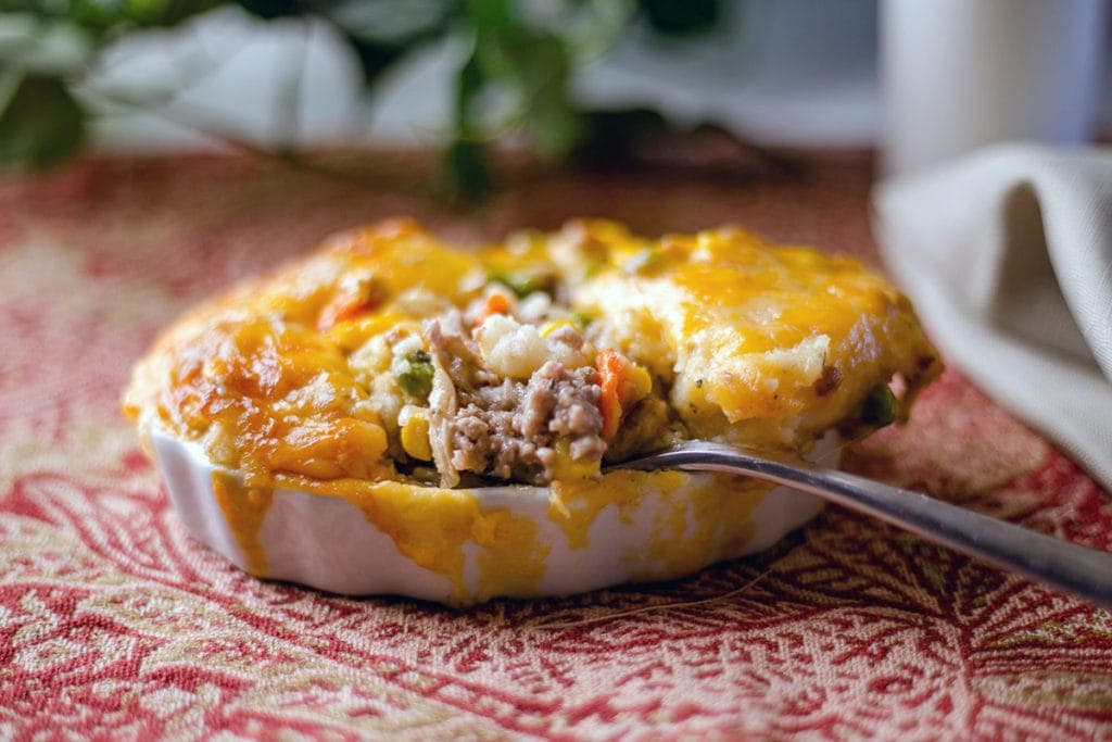 Shepherds pie in a white bowl on a red place mat