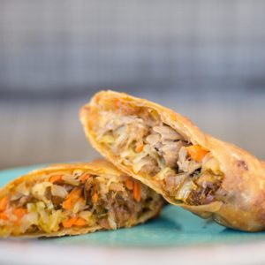 Homemade Egg Rolls on blue plate with blue background