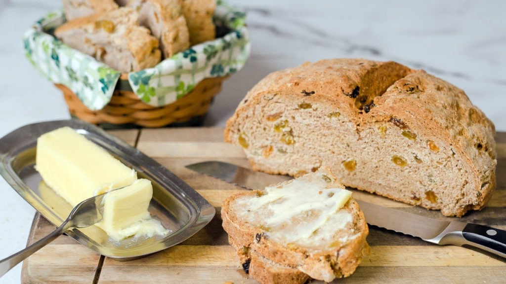 Irish Soda bread sliced on cutting board with butter