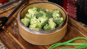 orange beef and broccoli in steamer basket