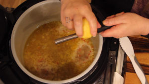 Zesting a lemon into the pot of shrimp scampi