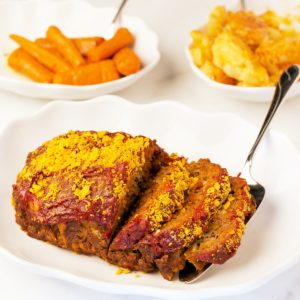 Cheesy Meatloaf sliced on a white platter with carrots and potatoes