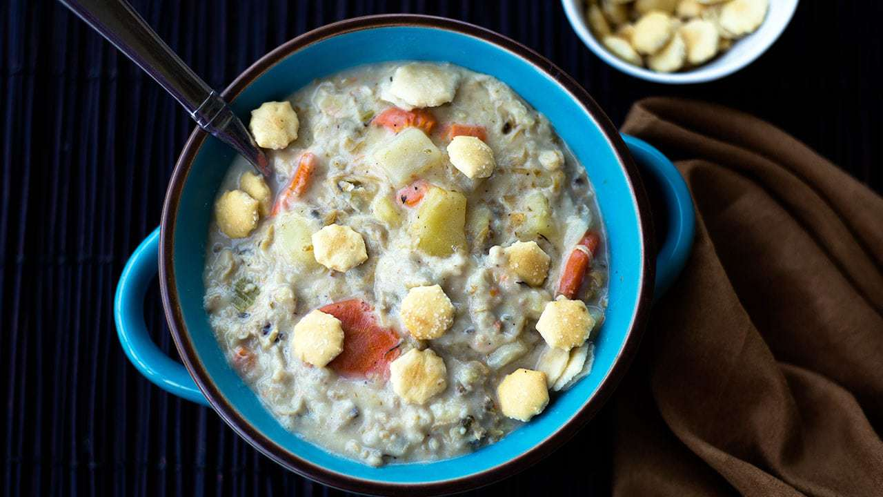 New England Clam Chowder in a blue bowl with oyster crackers and a spoon