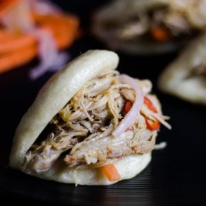 Asian Steamed Buns on a plate stuffed with Asian Pulled Pork and pickled vegetables