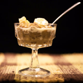 Banana caramel steel oats in a glass bowl with fresh bananas and cream