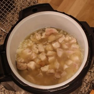 chicken and onions with stock in the Ninja Foodi pot for Chicken Carbonara