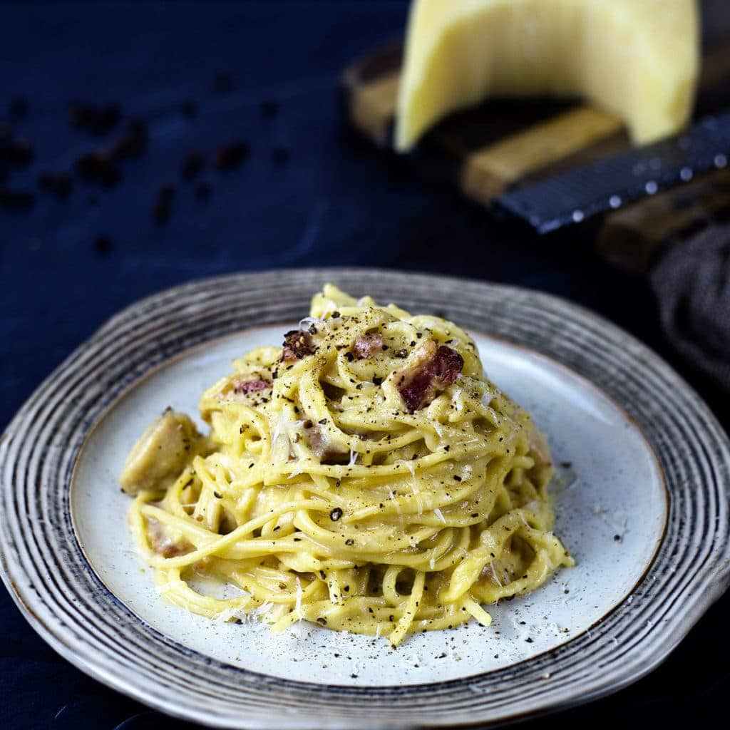 chicken carbonara on plate topped with parmesan cheese and cracked black pepper