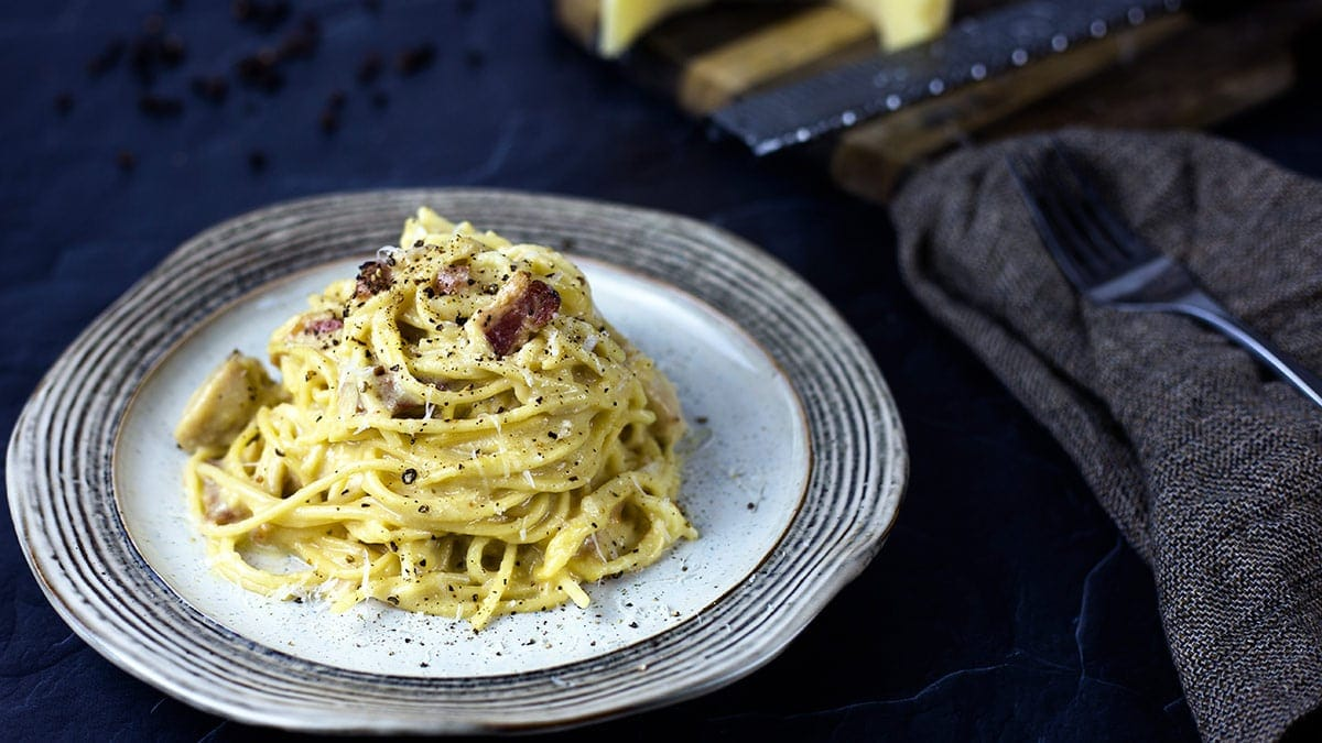 Chicken Carbonara on a plate topped with Parmesan and cracked black pepper
