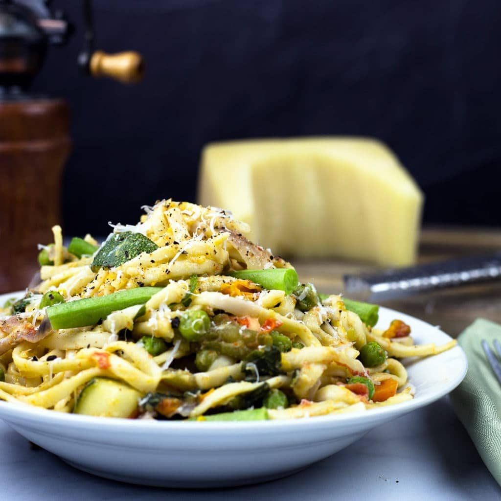 One Pot Pasta Primavera in a bowl topped with Parmesan cheese, cracked pepper