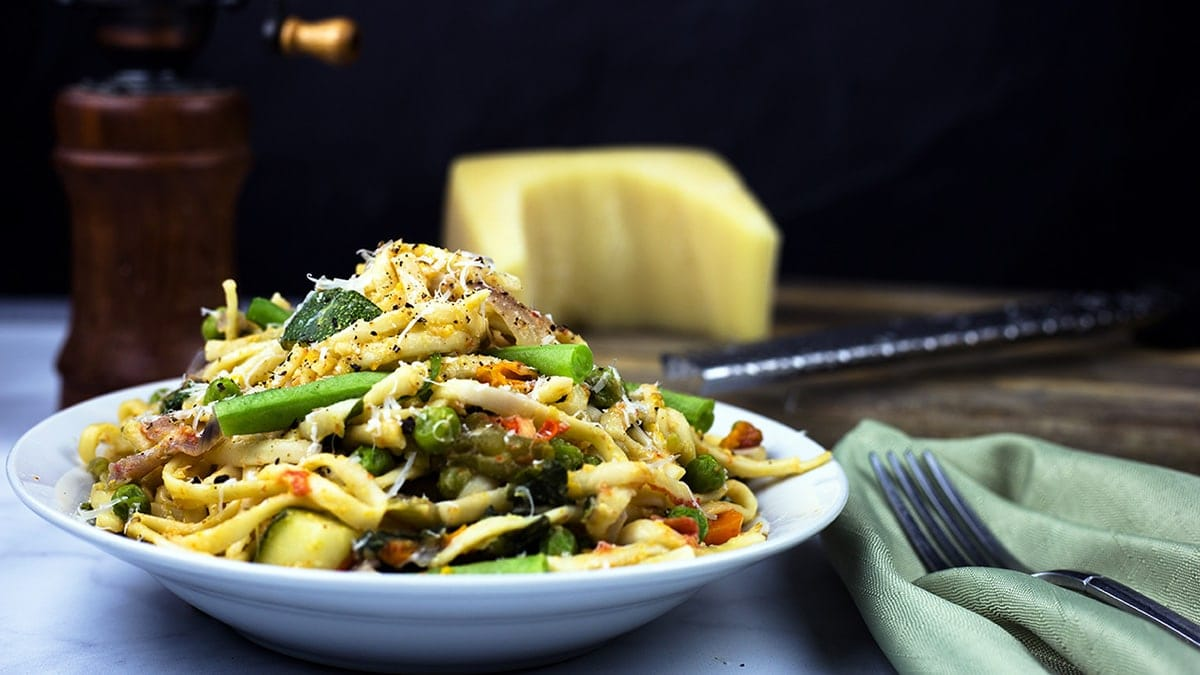 Pasta Primavera on a plate topped with grated parmesan and fresh pepper