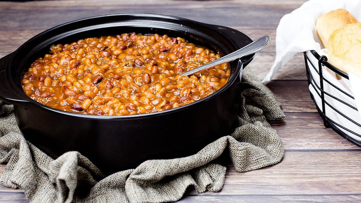 Pressure Cooker Baked Beans in a Black pot with a serving spoon