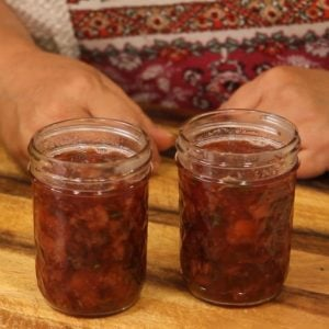 two jars of strawberry preserves on cutting board