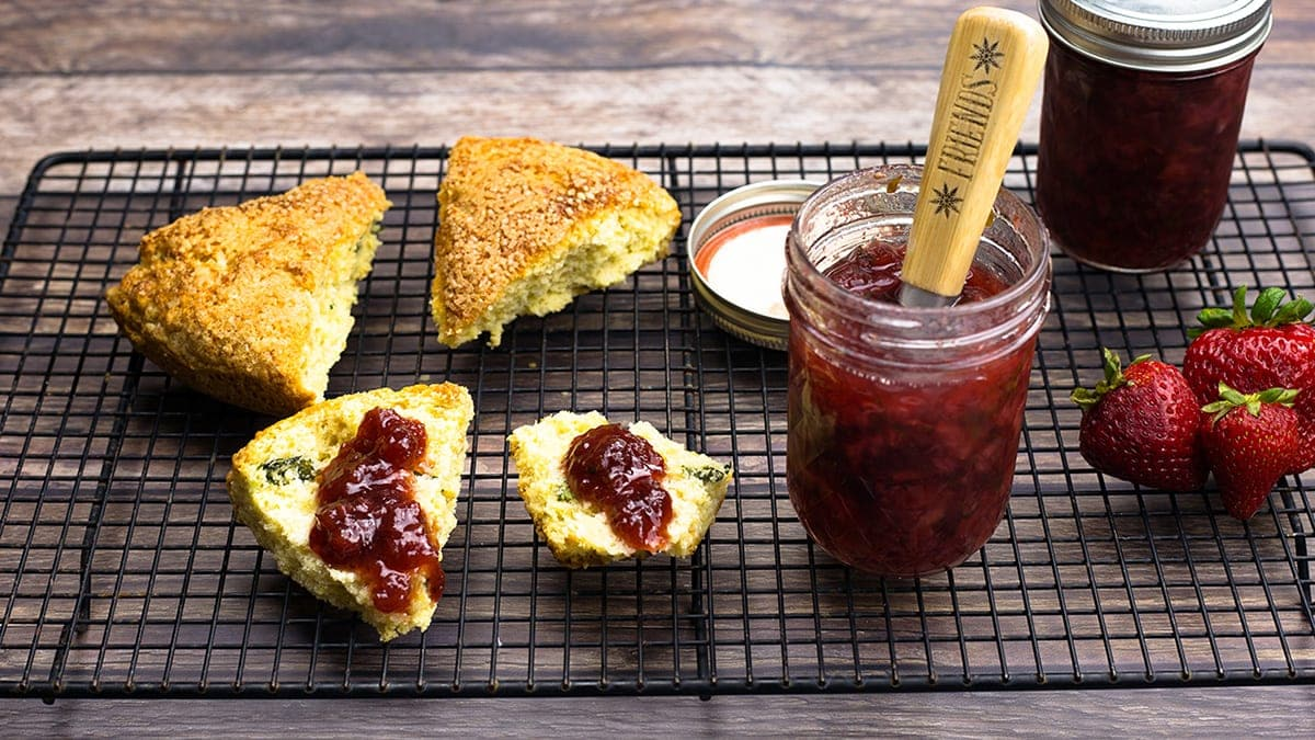 Strawberry preserves spread on scones on a cooling rack