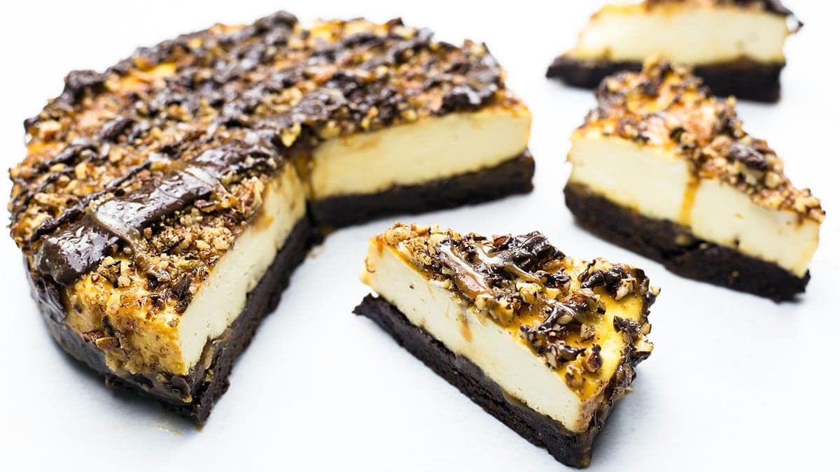 Turtle cheesecake with 3 slices on parchment