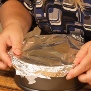 Covering Turtle Cheesecake with paper towel and foil