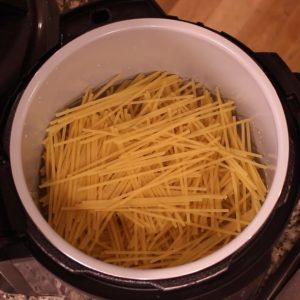 noodles layered in inner pot for one pot pasta primavera