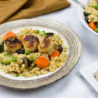 seared scallops on a bed of pearled couscous and vegetables.