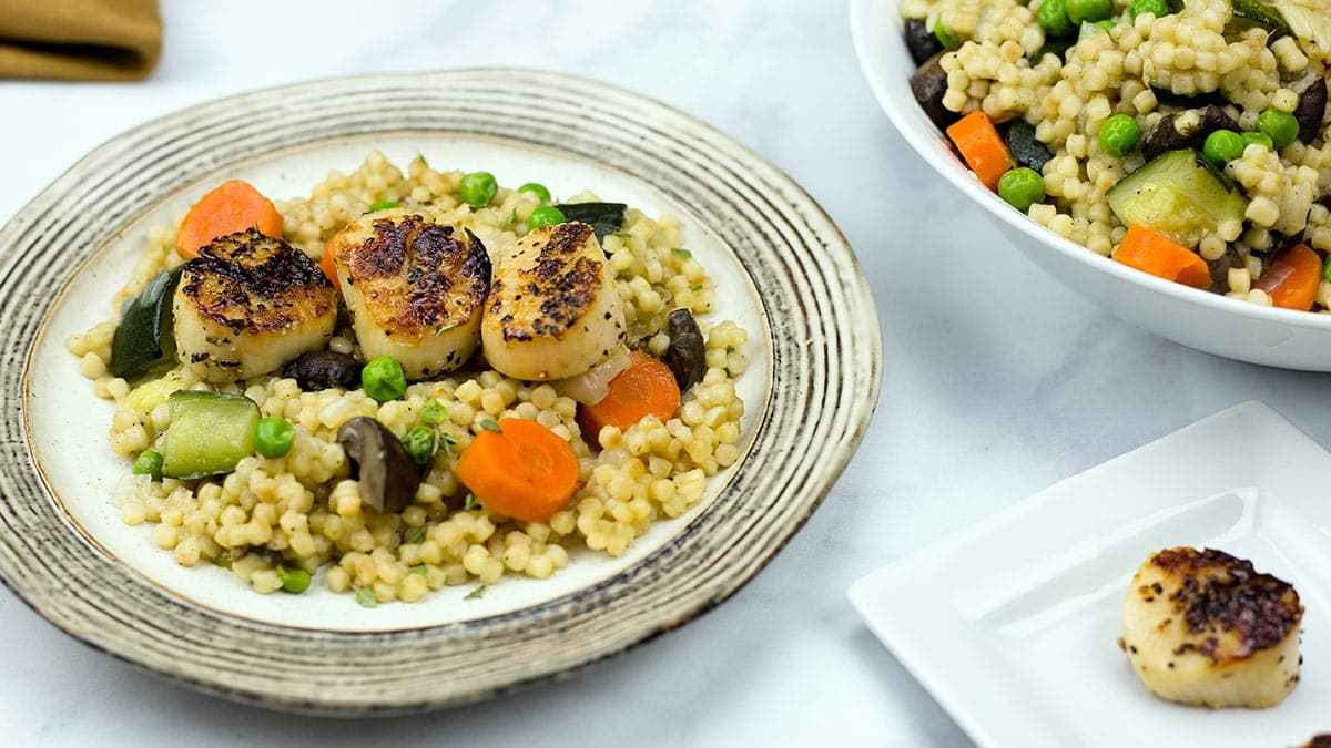Seared Scallops on a bed of couscous with vegetables