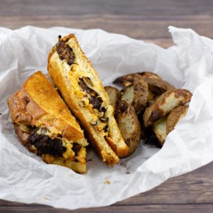 Patty Melt cut with fries on parchment