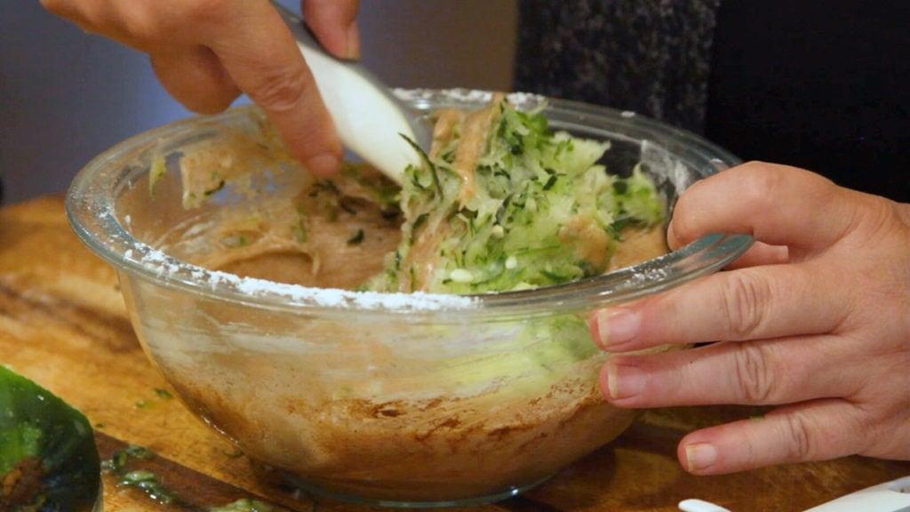 folding in grated zucchini into batter for zucchini bread