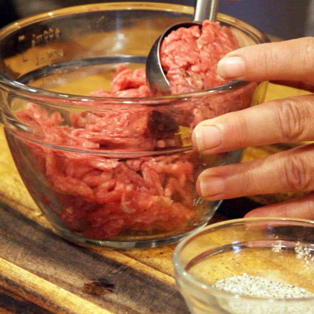 Scooping out ground beef for burgers