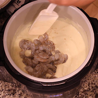 adding shrimp to the cauliflower cream sauce