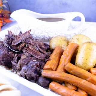 Pot roast on a platter with carrots and potatoes