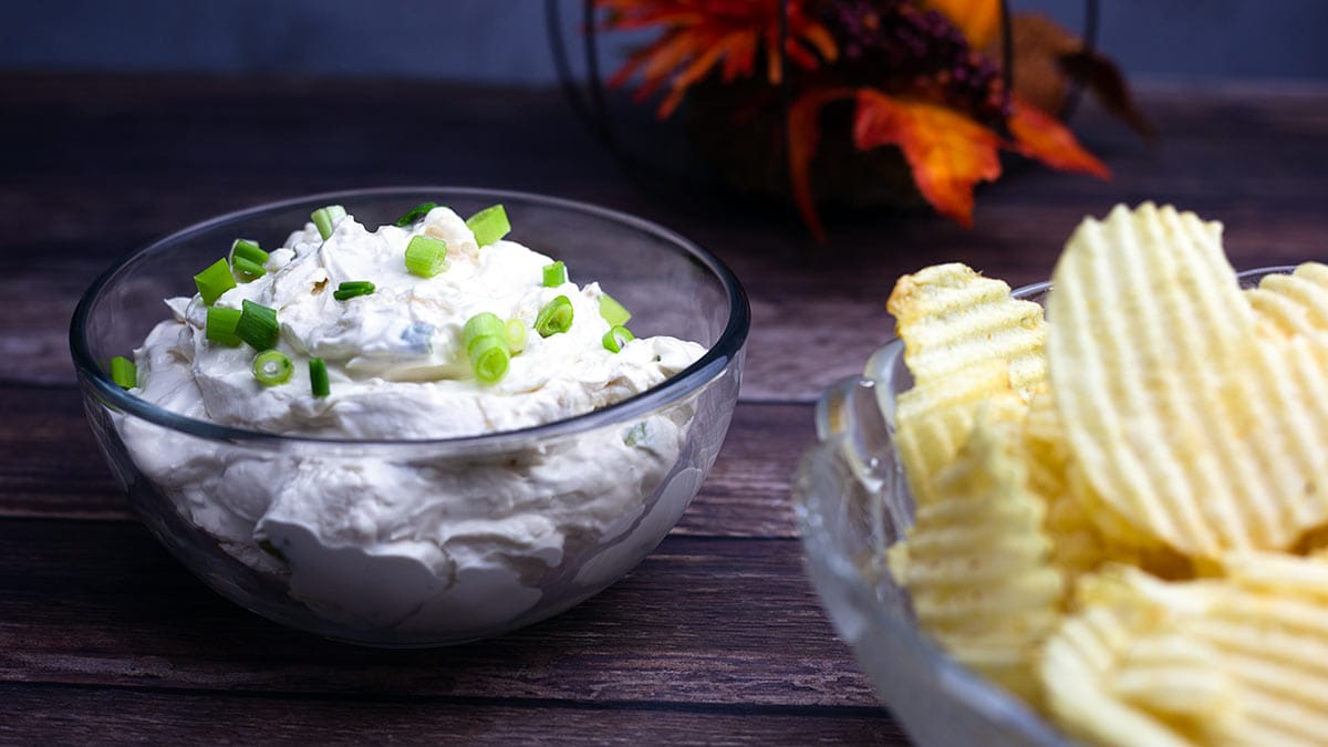 glass bowl of homemade French Onion Dip with a bowl of potato chips