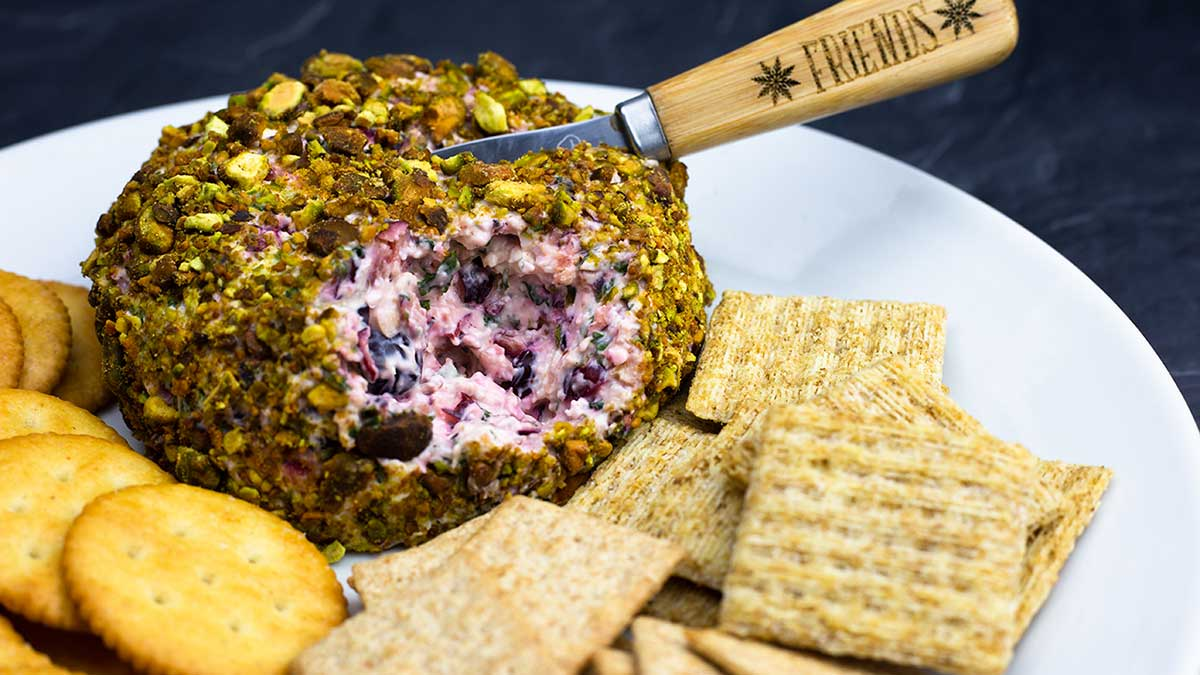 Cranberry Cheese Ball covered in pistachios on plate with crackers