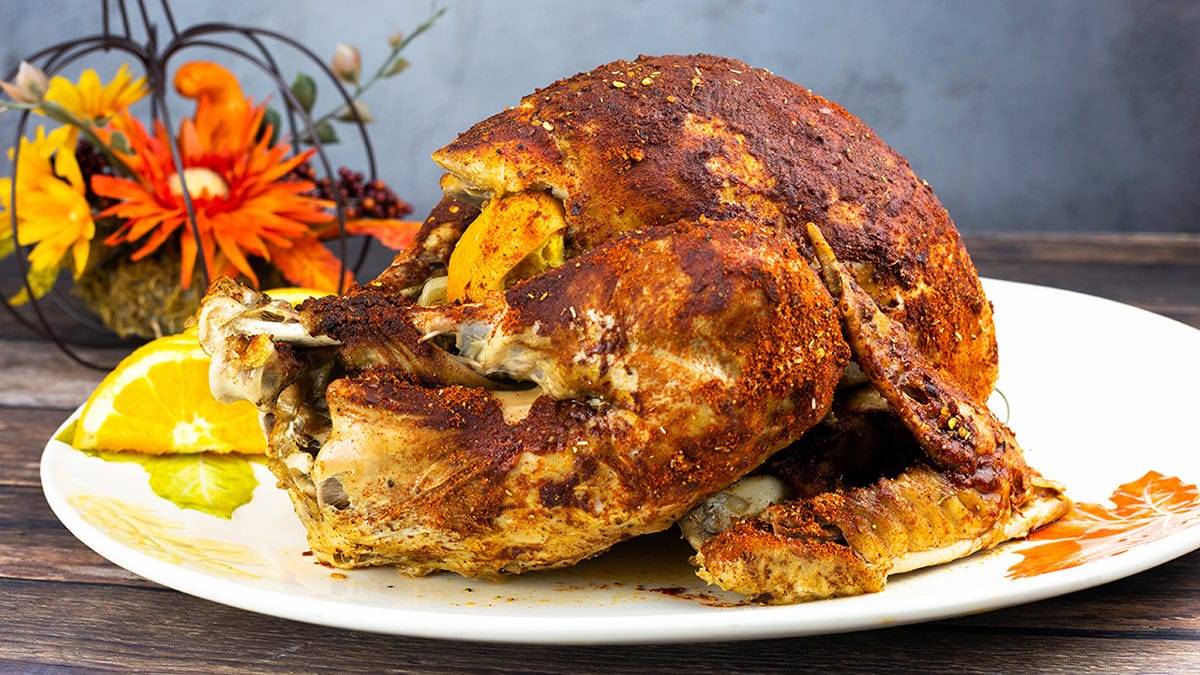 A whole turkey stuffed with aromatics sitting on a platter