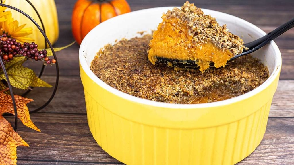 Sweet Potato Casserole with a pecan topping in a yellow serving dish