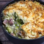 Ham and Broccoli Casserole with a scoop taken out in a black casserole dish