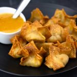 Air Fryer Crab Rangoon sitting next to a pineapple sweet and sour sauce