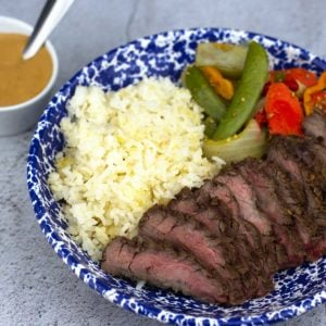 Asian steak 360 meal plated with peanut sauce in a bowl next to it
