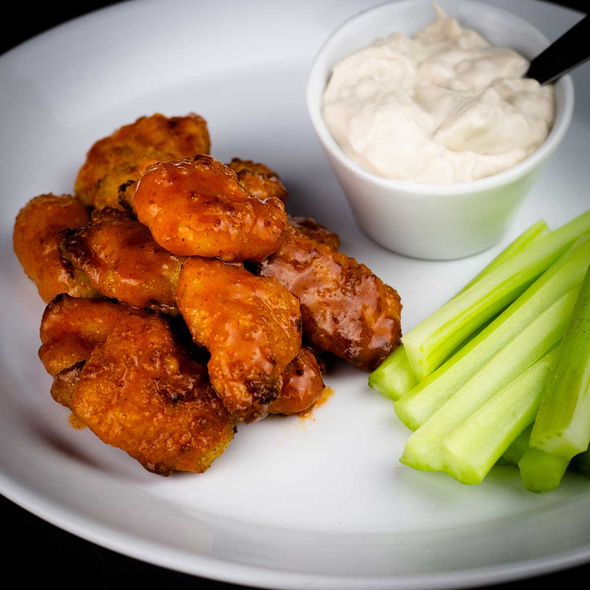Boneless buffalo wings on a white plate with celery and blue cheese dressing