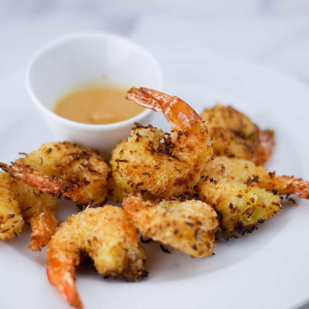 Air Fryer Coconut Shrimp on a plate with pineapple dipping sauce