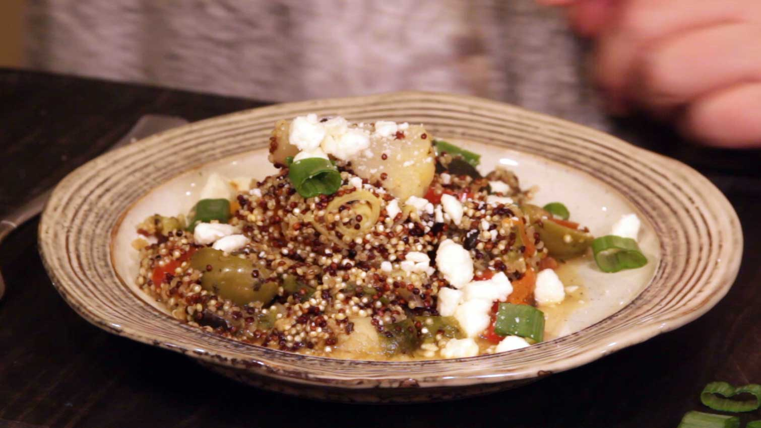 Plated Quinoa with vegetables with garnish of green onions and feta