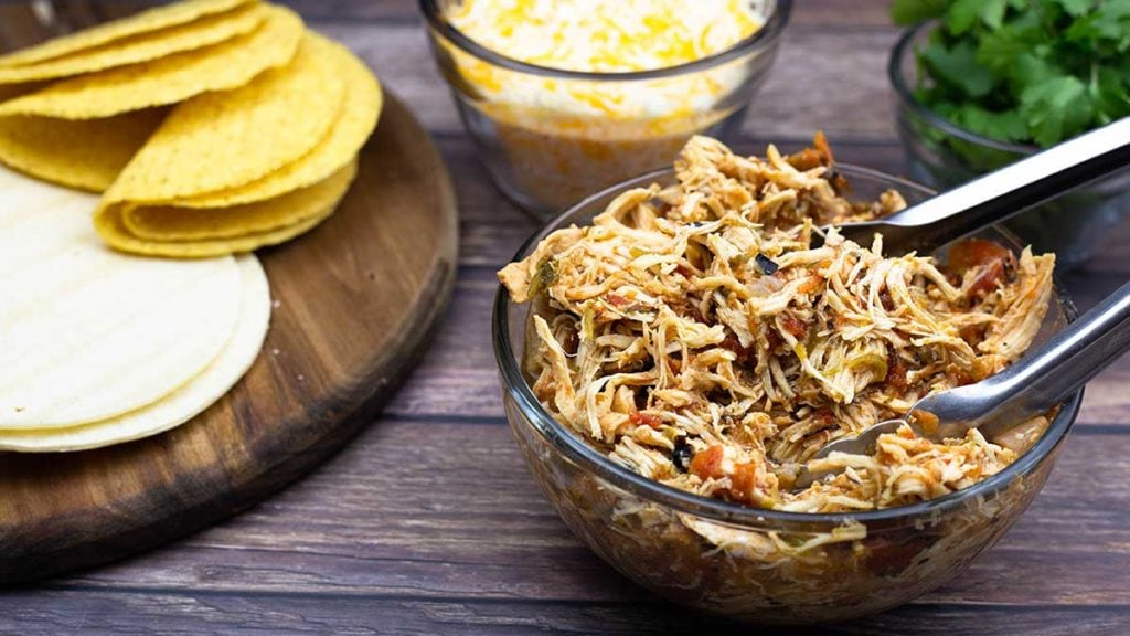 Mexican Shredded Chicken in a bowl next to tortillas, cheese, and cilantro