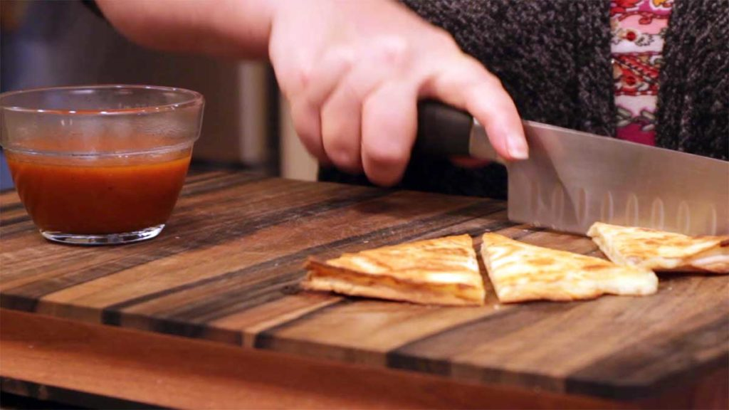Cutting cheese quesadillas for dipping into homemade enchilada sauce
