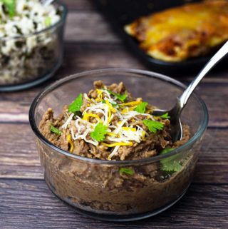 Glass bowl of refried beans with cheese and cilantro on top