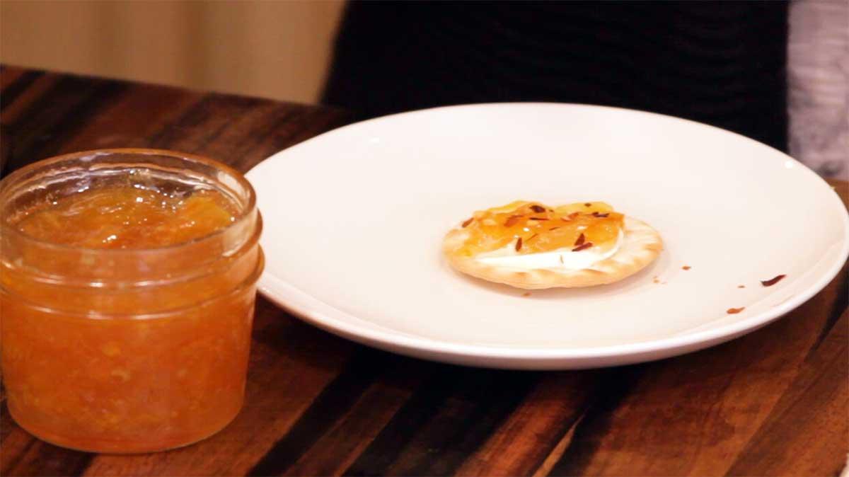 Serving orange marmalade on a cracker