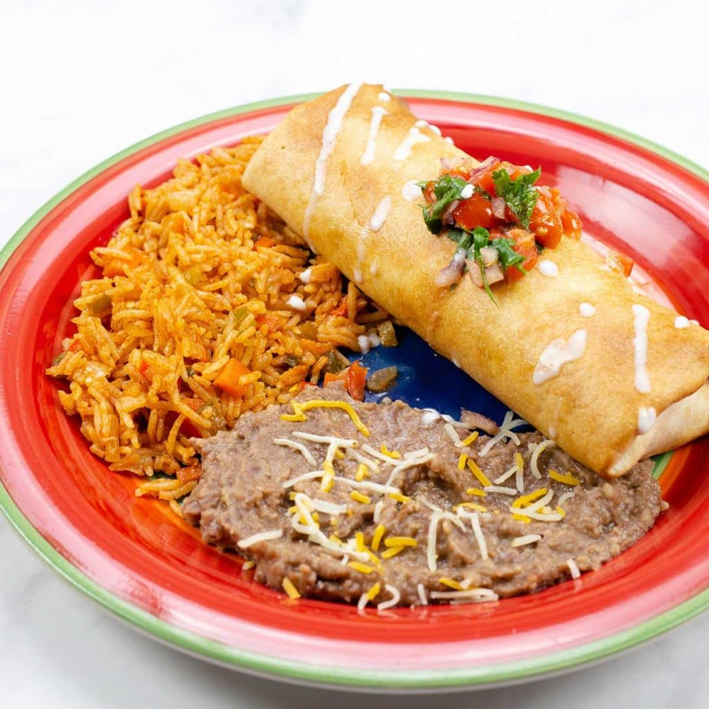 air fried chimichangas on a plate with beans and rice