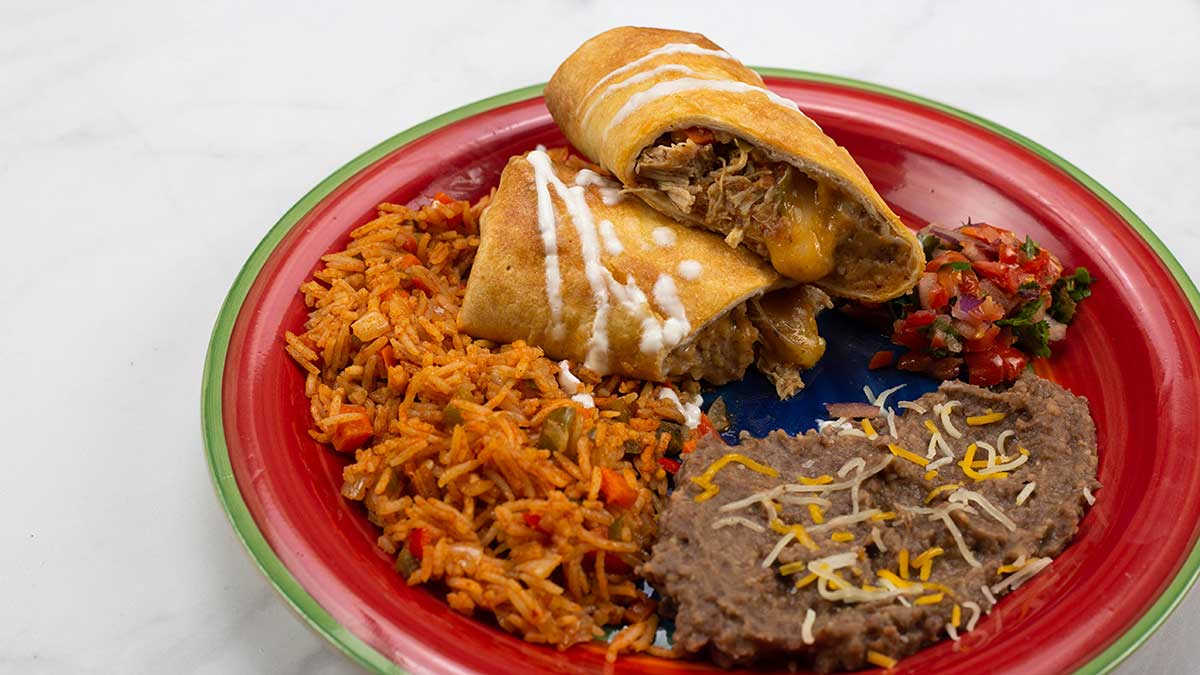 Air-Fried Chimichanga cut in half on a plate with rice and beans.